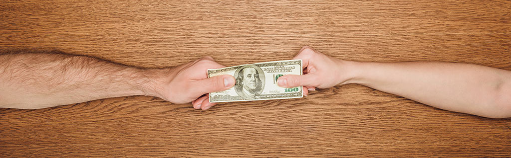 Two hands and arms pulling at American $100 bill - the fight over unclaimed property continues in October 2019