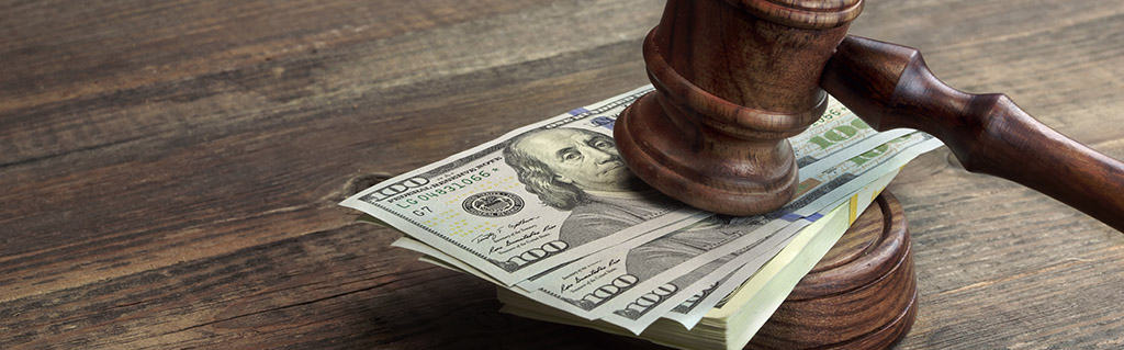 Gavel and cash on a wood desk