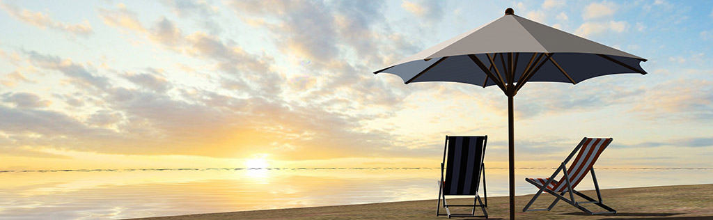 Beach chairs and umbrella on a beach at sunset